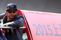 Mercedes Formula One driver Lewis Hamilton of Britain looks out from a bus during the drivers parade ahead of the Chinese F1 Grand Prix at the Shanghai International Circuit, April 12, 2015. REUTERS/Aly Song