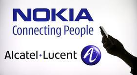 Женщина держит телефон на фоне экрана с логотипами Nokia и Alcatel Lucent. Париж, 14 апреля 2015 года. Финский производитель сетевого оборудования Nokia сообщил в среду, что достиг договоренности о приобретении французской Alcatel-Lucent. REUTERS/Benoit Tessier
