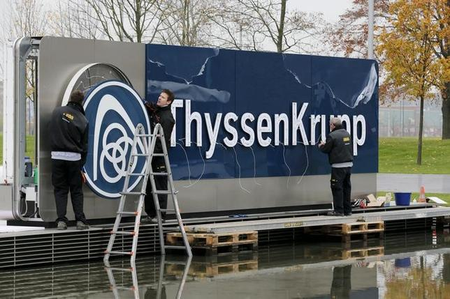Electricians carry a cover with the logo of ThyssenKrupp AG at the company's headquarters in the western German city of Essen November 19, 2014. REUTERS/Wolfgang Rattay