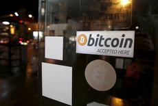 A bitcoin sticker is seen in the window of the 'Vape Lab' cafe, where it is possible to both use and purchase the bitcoin currency, in London March 24, 2015. REUTERS/Peter Nicholls
