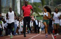 Jamaicano Usain Bolt (centro) corre com jovens na comunidade da Mangueira, no Rio de Janeiro, na quinta-feira. 16/04/2015 REUTERS/Ricardo Moraes
