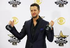 Singer Luke Bryan poses backstage with his awards for Vocal Event of the Year and Entertainer of the Year during the 50th Annual Academy of Country Music Awards in Arlington, Texas April 19, 2015.  REUTERS/Mike Stone