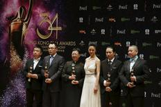 """The team including, Hong Kong director Ann Hui (3rd L) and Chinese actress Tang Wei (3rd R), pose with their trophies after winning the Best Film, Best Director, Best Cinematography, Best Art Direction and Best Costume & Make Up Design awards, for their movie """"The Golden Era"""", at the Hong Kong Film Awards in Hong Kong April 19, 2015. REUTERS/Bobby Yip"""