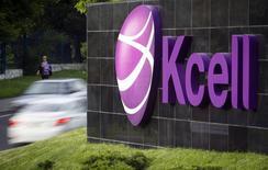 Автомобили проезжают мимо логотипа KCell у штаб-квартиры компании в Алма-Ате 23 мая 2013 года. Чистая прибыль крупнейшего мобильного оператора Казахстана Kcell в первом квартале 2015 года снизилась в годовом выражении на 15,4 процента до 13,234 миллиарда тенге ($71,2 миллиона), сообщила компания во вторник. REUTERS/Shamil Zhumatov