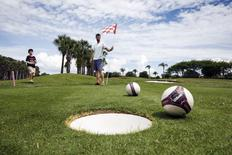 Patrick Wooten (C) holds the flag as his son Thomas, 11, misses his putt on the second half of the FootGolf course at Largo Golf Course in Largo, Florida April 11, 2015.  REUTERS/Scott Audette