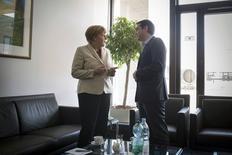 Le Premier ministre grec, Alexis Tsipras, a plaidé jeudi après un entretien avec la chancelière allemande Angela Merkel en marge d'un conseil européen à Bruxelles, en faveur d'une accélération des discussions en vue d'un accord permettant le versement de nouvelles aides à Athènes en échange de réformes structurelles. /Photo prise le 23 avril 2015/REUTERS/Bundesregierung/Guido Bergmann
