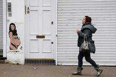 Mulher passa por pintura de princesa Kate grávida em rua de Londres. 23/4/2015   REUTERS/Cathal McNaughton