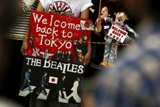 Fans hold puppets and a placard as they wait for the arrival of Paul McCartney before his gig at the Nippon Budokan Hall in Tokyo April 28, 2015.  REUTERS/Thomas Peter