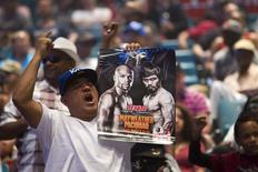 A man holds up a fight poster as fans wait for undefeated WBC/WBA welterweight champion Floyd Mayweather Jr. of the U.S. at the MGM Grand Arena in Las Vegas, Nevada April 28, 2015.  REUTERS/Las Vegas Sun/Steve Marcus