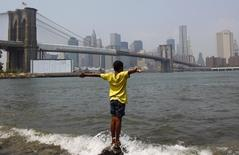 A boy stands in the water to cool off on a shore near the Brooklyn Bridge in Brooklyn, New York, July 21, 2011.   REUTERS/Mike Segar