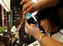 Salon de coiffure à Pékin. La croissance dans le secteur des services a ralenti en avril en Chine, à un rythme plus important qu'en mars, autre signe d'inquiétude quant au rythme général de l'économie. L'indice officiel des directeurs d'achats (PMI) du secteur est tombé à 53,4 en avril, contre 53,7 en mars. /Photo d'archives/REUTERS/Jason Lee