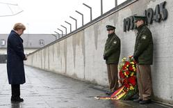 German Chancellor Angela Merkel observes a moment of silence as she lays a wreath during a ceremony at the memorial in the former German Nazi concentration camp in Dachau near Munich, Germany May 3, 2015, to mark the 70th anniversary of the liberation of the camp by the U.S. army on April 29, 1945.    REUTERS/Michaela Rehle