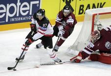 Canada's Sidney Crosby challenges Latvia's Rodrigo Abols and goalkeeper Ervins Mustukovs (L-R) during their Ice Hockey World Championship game at O2 arena in Prague, Czech Republic May 1, 2015. REUTERS/David W Cerny