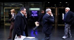 Unas personas pasan junto a una casa de monedas en el centro de Buenos Aires, jun 1 2012. Las monedas latinoamericanas, que se estabilizaron el mes pasado lideradas por el real brasileño, podrían sufrir un nuevo remezón si los datos del empleo estadounidense que se conocerán el viernes confirman las expectativas sólidas que anticipan los economistas. REUTERS/Marcos Brindicci
