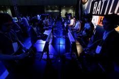 """Le jeu """"Battlefield Hardline"""" à l'essai au salon du jeu vidéo de Tokyo. L'éditeur de jeux vidéo Electronic Arts a annoncé mardi un chiffre d'affaires et un bénéfice supérieurs au consensus pour le quatrième trimestre, soutenus par des ventes numériques solides et par la sortie du jeu """"Battlefied Hardline"""". /Photo prise le 18 septembre 2014/ REUTERS/Yuya Shino"""