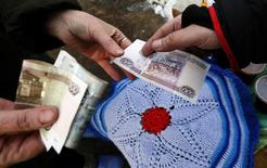 A vendor (L) takes a Russian rouble banknote from a customer buying a handmade woolen rug in the village of Shoshino in Krasnoyarsk region, Siberia, March 17, 2015. Russia's rouble edged higher early on Wednesday, as exporters selling foreign currency in preparation for tax payments to the state budget narrowly outweighed the drag from lower oil prices. Picture taken March 17, 2015.  REUTERS/Ilya Naymushin (RUSSIA - Tags: BUSINESS SOCIETY)