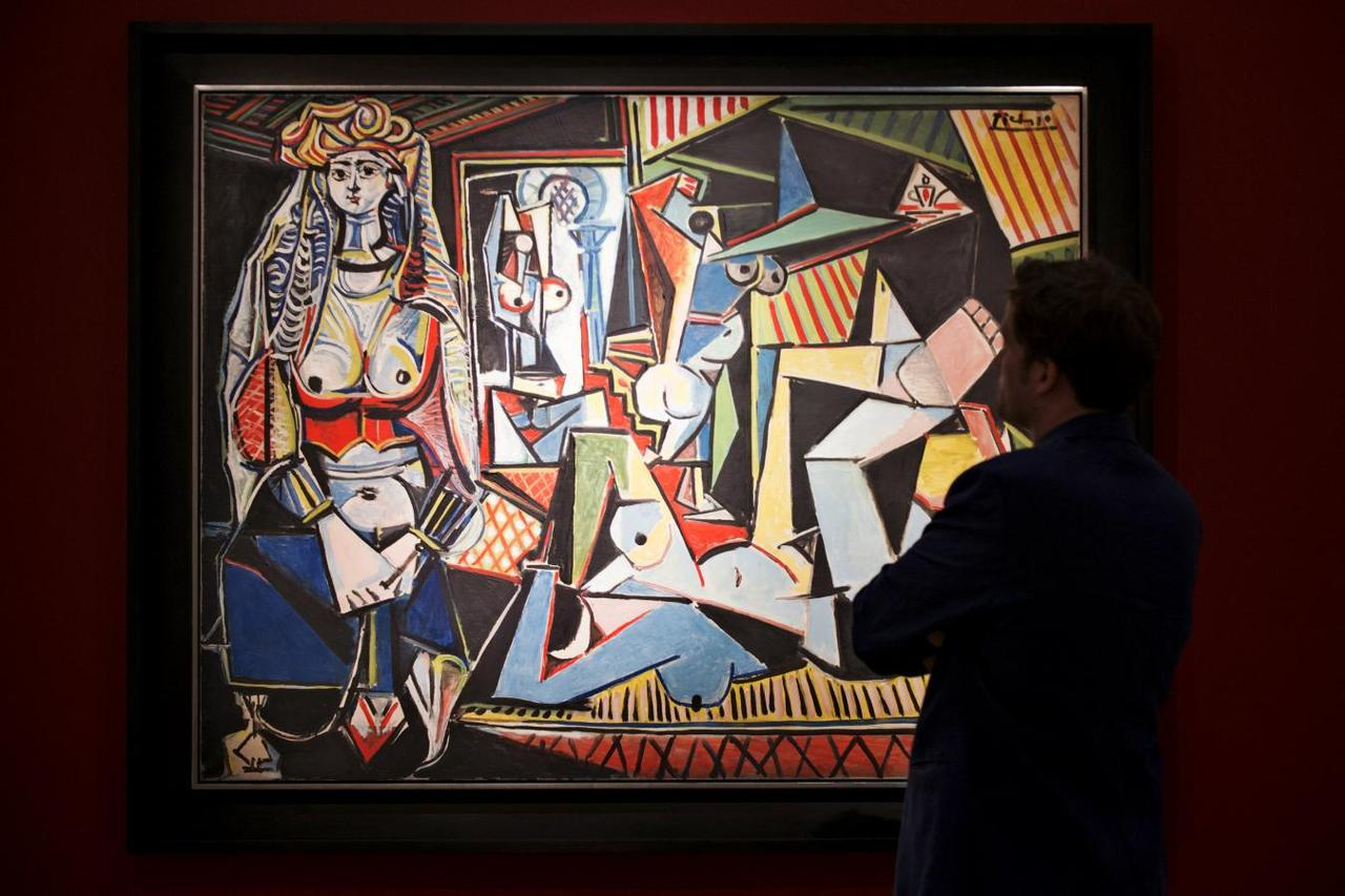 A man pauses to look at pablo picassos les femmes dalger version o women of algiers estimated at 140 million at a media preview for christies