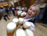 Официантка с кружками пива на Октоберфесте. Мюнхен, 20 сентября 2014 года. Прибыль пивоваренной компании SABMiller за год превысила ожидания аналитиков за счет улучшения показателей во второй половине 2014/2015 финансового года. REUTERS/Michael Dalder