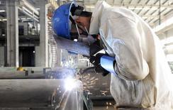 Un empleado solda el exterior de un vehículo en una línea de producción en una fábrica en Qingdao, provincia de Shandong, 1 de diciembre de 2014. La producción industrial de China creció un 5,9 por ciento en abril respecto al mismo mes del año anterior, ligeramente por debajo de las previsiones, lo que refuerza las expectativas de que Pekín tendrá que redoblar sus esfuerzos para apuntalar a la enfriada economía. REUTERS/China Daily