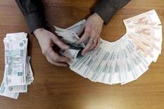 Сотрудница ставропольской компании считает рубли. Ставрополь, 17 декабря 2014 года. Рубль в среду обновил максимум текущего года в паре с долларом, отправив его на уровень 48,83 впервые с ноября, на фоне дорожающей нефти и слабости американской валюты, а также в надежде на снижение конфронтации России с Западом. REUTERS/Eduard Korniyenko