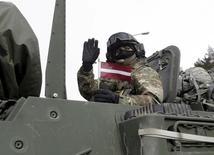 """Солдат 2-го кавалерийского полка армии США с латвийским флагом во время учений """"Драгунский рейд"""". Лиепупе, 22 марта 2015 года. Польша и страны Балтии сообщили о намерении добиться постоянного присутствия войск НАТО на своей территории, чтобы противостоять возросшей военной активности России в море и воздухе, и, согласно внутреннему документу польских властей, этот вопрос может быть поднят в следующем году на саммите в Варшаве. REUTERS/Ints Kalnins"""
