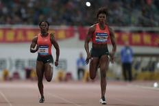 Nigeria's Blessing Okagbare-Ighoteguonor (R) runs next to Jamaica's Shelly-Ann Fraser-Pryce during the women's 100m race at the IAAF Diamond League Athletics in Shanghai May 17, 2015. REUTERS/Aly Song