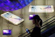 Una que mujer sostiene un Iphone de Apple, pasa junto a una publicidad del Samsung Galaxy S6, en un mall en Singapur, 24 de abril de 2015. Un tribunal de apelación estadounidense revirtió parte de un fallo por 930 millones de dólares que Apple ganó en 2012 frente a Samsung Electronics, argumentando que la apariencia comercial no puede ser protegida.  REUTERS/Edgar Su