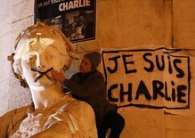 """A man touches the spray-painted shut mouth of a statue near a poster reading """"I am Charlie"""" as he takes part in a solidarity march (Marche Republicaine) in the streets of Paris January 11, 2015. REUTERS/Charles Platiau"""