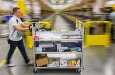 Un trabajador de Amazon ordena unos paquetes en su centro de logística en Brieselang, Alemania, nov 11 2014. La unidad de Amazon en Alemania pagó el año pasado sólo unos 16 millones de dólares en impuestos pese a registrar 11.900 millones de dólares en ventas a clientes en ese país europeo, según datos publicados por el regulador.  REUTERS/Hannibal