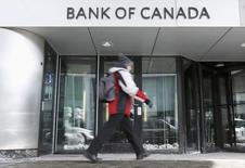 Прохожий у здания Банка Канады в Оттаве. 4 марта 2015 года. Банк Канады в среду оставил ключевую ставку на уровне 0,75 процента годовых, проигнорировав слабые американские данные за первый квартал и заявив, что стабильный рост в США в этом квартале поддержит канадский экспорт и инвестиции. REUTERS/Chris Wattie