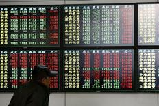 Un inversor mira la información mostrada en una pantalla electrónica en una agencia de la bolsa, en Shanghai 8 de diciembre de 2014. Los mercados bursátiles chinos se desplomaron el jueves y los índices bajaron más de un 6 por ciento con volúmenes récord, por una ola de ventas disparada por la decisión de importantes corredurías de aumentar las garantías requeridas en ciertas transacciones. REUTERS/Aly Song