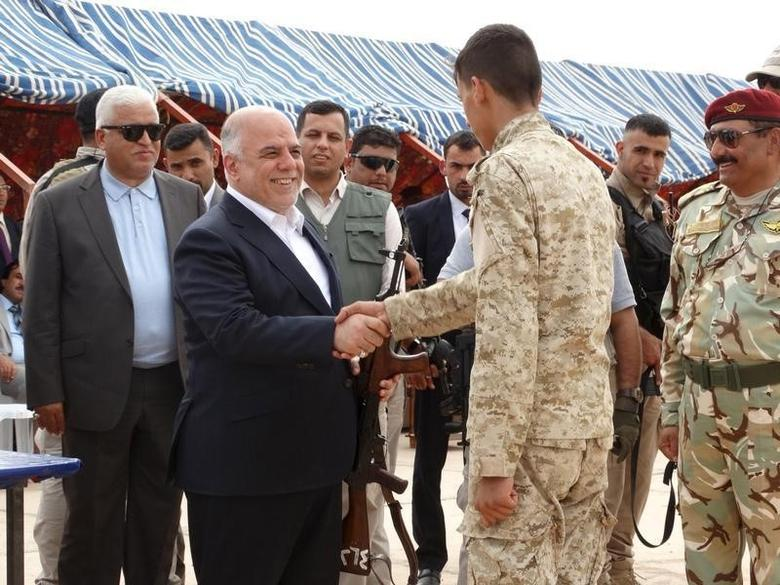 File photo of Prime Minister Haidar al-Abadi (L) as he shakes hands with a Sunni tribesman at Camp Habbaniyah, in the eastern city of Ramadi April 8, 2015. REUTERS/Stringer