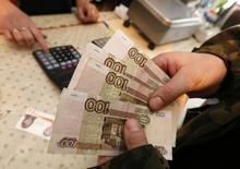 """A customer holds 100-rouble banknotes while visiting a local grocery store in the village of Verkhnyaya Biryusa outside the Russian Siberian city of Krasnoyarsk, January 23, 2015. The Russian rouble is set to appreciate """"dramatically"""" following a period of volatility, Russia's First Deputy Prime Minister Igor Shuvalov said on Friday at the World Economic Forum in Davos. The rouble has lost half of its value against the dollar since the start of last year as a result of plunging oil prices and Western sanctions imposed as a result of the Ukraine crisis, but Russian officials have argued that it is below its fair value. REUTERS/Ilya Naymushin (RUSSIA  - Tags: BUSINESS)"""
