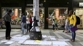 Pessoas olhando ofertas de emprego coladas em um poste no centro de São Paulo.  19/03/2015     REUTERS/Paulo Whitaker
