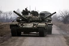 Пророссийские повстанцы буксируют поврежденный танк в сторону поселка Чернухино 12 марта 2015 года. Пять украинских военнослужащих и 15 мирных жителей и повстанцев погибли в результате боев на востоке Украины в среду, сообщили помощник президента Украины и представители сепаратистов. REUTERS/Marko Djurica