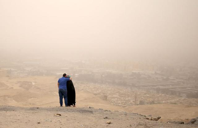 A couple hugs while standing on a hilly area overlooking Cairo on a dusty and hazy day where temperatures reached 46 degrees Celsius (114 Fahrenheit) May 27, 2015.  REUTERS/Asmaa Waguih