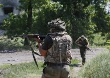 Украинские военнослужащие патрулируют территорию в Марьинке 5 июня 2015 года. Ситуация в области безопасности на Украине ухудшилась в последние дни, так как обе стороны конфликта продолжают подвергать мирное население риску, располагая войска вблизи гражданских объектов, заявили в пятницу международные наблюдатели. REUTERS/Gleb Garanich