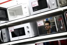 Un hombre reflejado en un microondas, en una tienda en Madrid, el 17 de abril de 2015. La demanda de los hogares y la inversión fueron los principales factores que impulsaron el crecimiento económico en la zona euro en el primer trimestre, según datos difundidos el martes por la oficina estadística de la Unión Europea, que confirmó sus estimaciones de crecimiento anteriores. REUTERS/Susana Vera