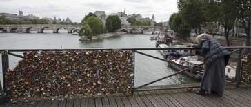 "A woman takes pictures of a remaining iron grill panel covered with ""love locks"" on the Pont des Arts which crosses over the River Seine in Paris, France, June 1, 2015. The bridge is closed from June 1 to June 8 and the iron grills covered with padlocks which hang on the 19th century pedestrian bridge will be removed by city municipal employees. REUTERS/Philippe Wojazer"
