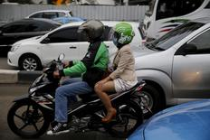 A Gojek driver pillions a customer as he rides his motorcycle through a business district street in Jakarta, June 9, 2015. REUTERS/Beawiharta