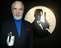 """British actor Christopher Lee, who played the part of Bond bad guy Scaramanga in the film """"The Man with the Golden Gun"""", poses for pictures with the original gun from the James Bond film at the Science Museum in London, in this file photograph dated October 15, 2002. REUTERS/Russell Boyce/files"""