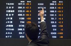 A man points at market indices at the Tokyo Stock Exchange (TSE) in Tokyo June 11, 2015.  REUTERS/Thomas Peter