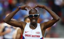 Mohamed Farah of Britain celebrates as he crosses the finish line to win the men's 5000 metres final during the European Athletics Championships at the Letzigrund Stadium in Zurich August 17, 2014. REUTERS/Arnd Wiegmann