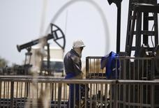Рабочий у станка-качалки в Баку 16  июня 2015 года. Цены на нефть слабо растут на фоне повышения спроса при сохранении высокого объема добычи. REUTERS/Kai Pfaffenbach