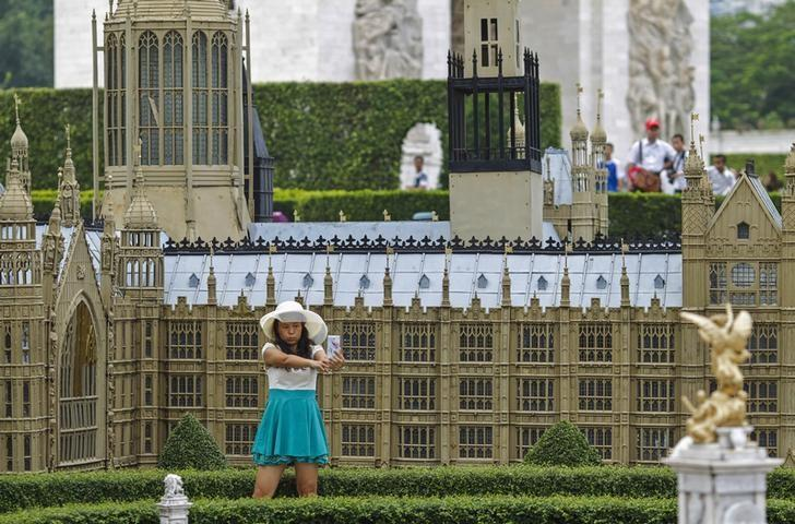 A woman poses for a selfie in front of a miniature replica of London's Houses of Parliament, at a theme park called ''Window Of The World'' in Shenzhen, Guangdong province, October 20, 2014. REUTERS/Alex Lee