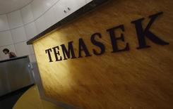 A woman passes a logo of state investor Temasek Holdings at their office in Singapore July 8, 2014.  REUTERS/Edgar Su