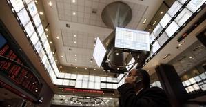 Un hombre habla por celular mientras mira un tablero electrónico que muestra el índice Bovespa de la Bolsa de Sao Paulo, en Brasil, 4 de agosto de 2011. El principal índice de la bolsa de Brasil subía el miércoles apoyado en un alza de las acciones de la petrolera Petrobas y la minera Vale, que protegía al Bovespa de una indicación del Banco Central que apunto a tasas de interés más altas y de un escenario externo adverso. REUTERS/Nacho Doce