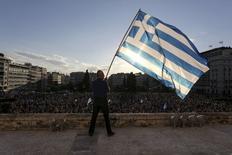 Una persona sostiene una bandera de Grecia en una manifestación frente al Parlamento en Atenas, jun 22 2015. Grecia y sus acreedores internacionales están en las fases finales de las conversaciones que buscan reformas de Atenas a cambio de un financiamiento que le evite incumplir un pago al Fondo Monetario Internacional (FMI) el martes. REUTERS/Yiannis Liakos/Intimenews