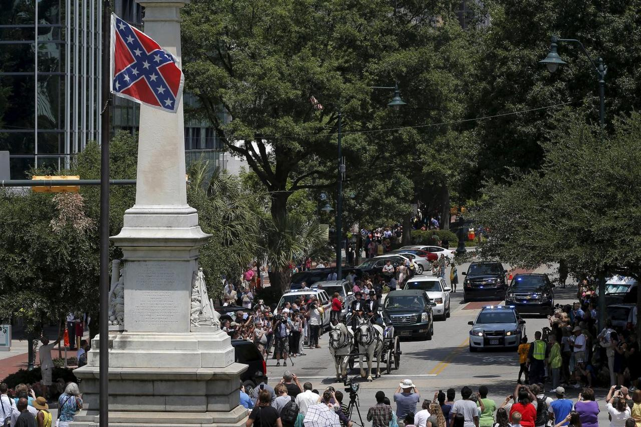 Confederate symbols of civil war divide us 150 years on a horse drawn carriage carries the casket of the late south carolina state senator clementa pinckney past the confederate flag and onto the grounds of the biocorpaavc Choice Image
