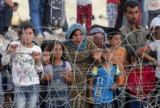 Sírios curdos de Kobani aguardam atrás de cerca para cruzar fronteira com Turquia.  25/6/2015.   REUTERS/Murad Sezer